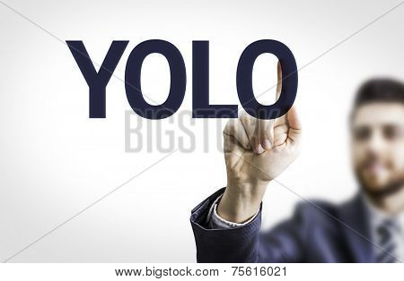 Business man pointing to transparent board with text: YOLO (you only live once)