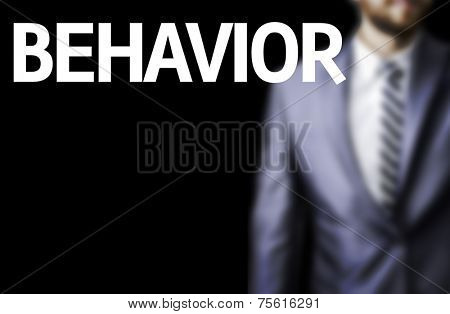 Behavior written on a board with a business man on background