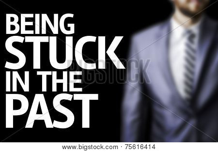 Being Stuck In the Past written on a board with a business man on background