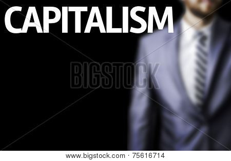 Capitalism written on a board with a business man on background