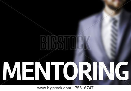 Mentoring written on a board with a business man on background