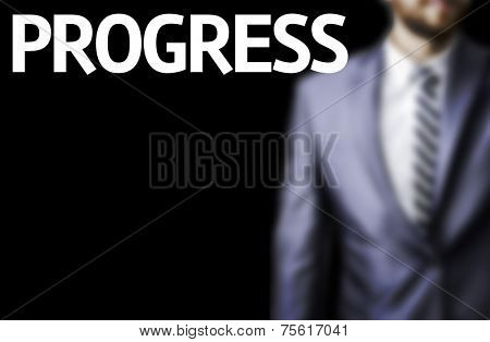 Progress written on a board with a business man on background