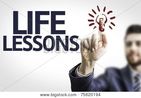 Business man pointing to transparent board with text: Life Lessons