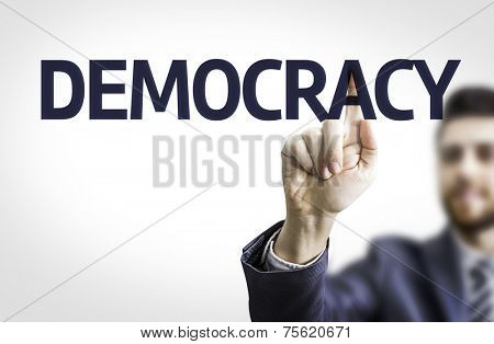 Business man pointing to transparent board with text: Democracy