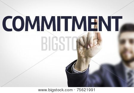 Business man pointing to transparent board with text: Commitment