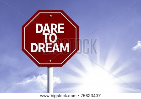 Dare to Dream written on red road sign with a sky on background