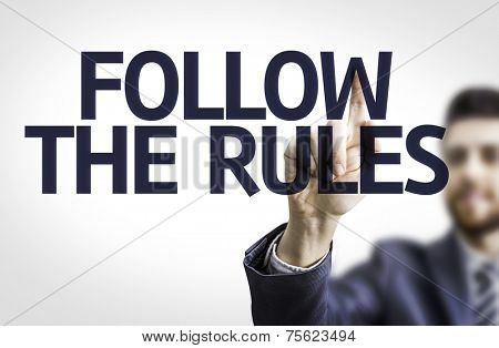 Business man pointing to transparent board with text: Follow the Rules