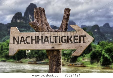 Sustainability (In German) wooden sign with a forest background