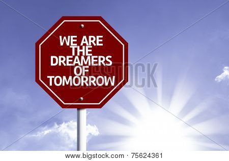 We Are The Dreamers Of Tomorrow written on red road sign with a sky on background