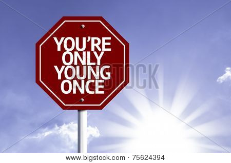 You're Only Young Once written on red road sign with a sky on background