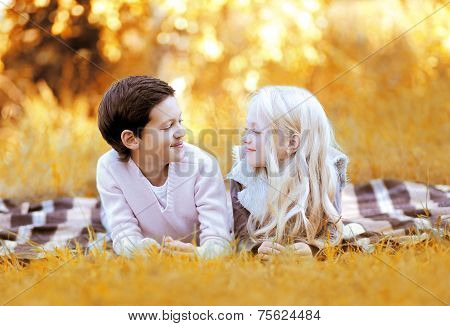 Happy Boy And Little Girl Lying On The Plaid Having Fun In Warm Sunny Autumn Day