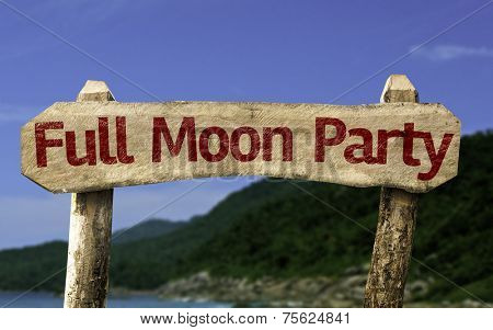 Full Moon Party wooden sign with a beach on background