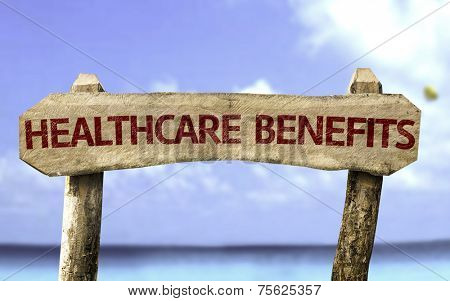 Healthcare Benefits wooden sign with a beach on background