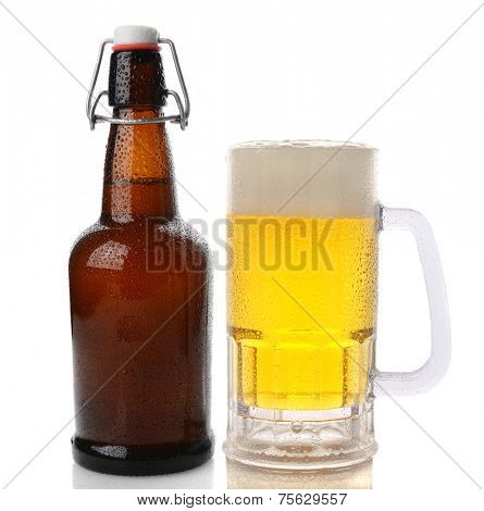 Closeup of a Mug of beer with a frothy head next to a swing top brown beer bottle. Straight on shot on a white background with reflection. Both items are cover with water drops.