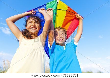 Little girl and little boy playing kite together.