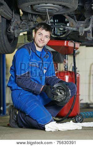 auto repairman mechanic portrait with axle reduction gear in car auto repair or maintenance shop service station