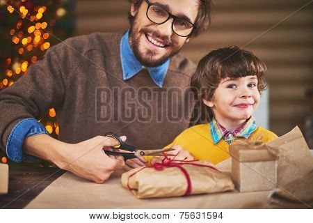 Handsome man and his son looking at camera while packing xmas gifts