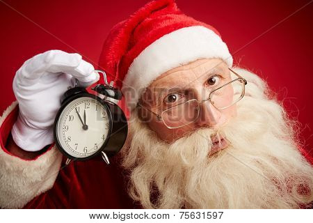 Serious Santa holding clock showing five minutes to xmas