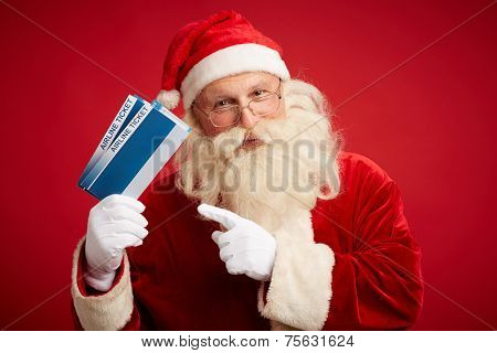 Kind Santa Claus with two airline tickets looking at camera over red background