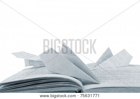 Origami airplanes on old book, on white background
