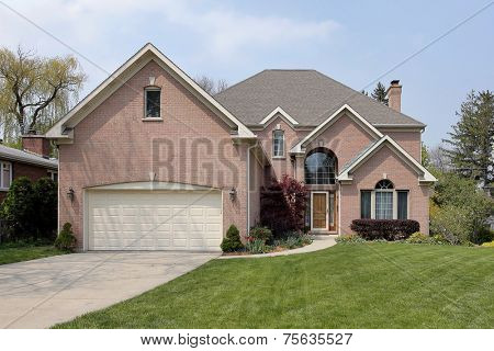 Suburban brick home with arched window above entry