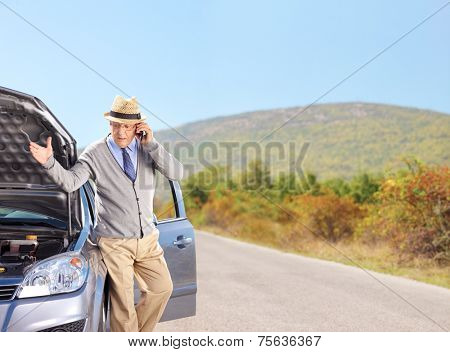 Senior having a problem with his car on an open road shot with a tilt and shift lens