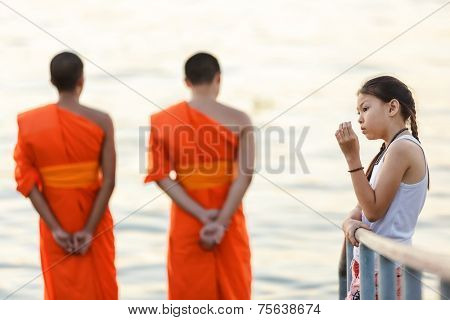 BANGKOK, THAILAND, FEBRUARY 9, 2011: Two Buddhist monks are watching the sunset on the river while a thoughtful little girl is standing near a fence in the Thewet district of Bangkok, Thailand