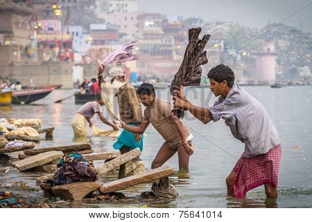 VARANASI, INDIA - MARCH 21, 2013: A washer is working in the holy water of the river Ganges, in Varanasi