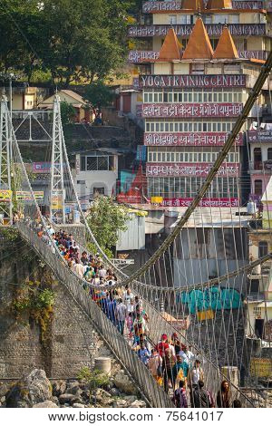 RISHIKESH, INDIA - 2012 NOVEMBER 13: People crossing Lakshman Jhula bridge over Ganges on November 13, 2012 in Rishikesh, India.