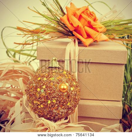 some gift boxes tied with natural raffia of different colors and topped with a flower, and a christmas ball, with a retro effect