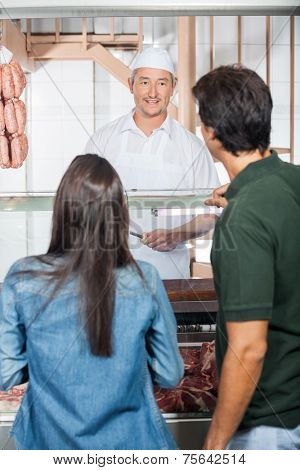 Mature couple buying meat from butcher shop