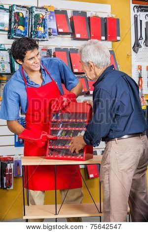 Smiling salesman showing tools to senior man in hardware store