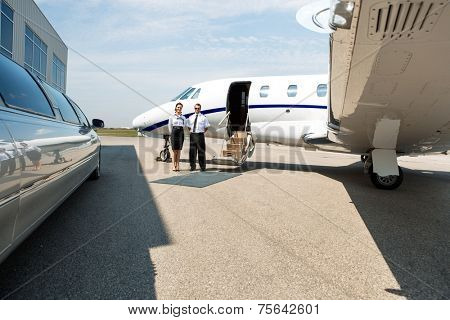 Stewardess and pilot standing neat limousine and private jet at airport terminal