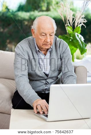 Senior man using laptop while sitting on couch at nursing home porch