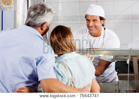 Friendly male butcher looking at customers in shop