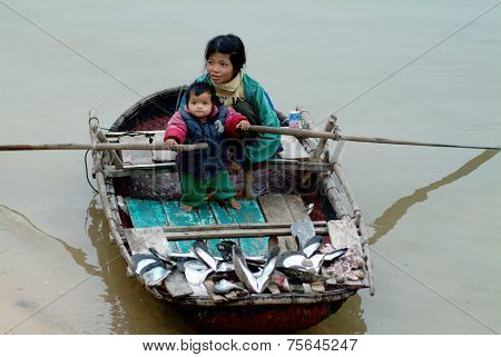 Vietnamese young woman selling souvenir shell on her boat.
