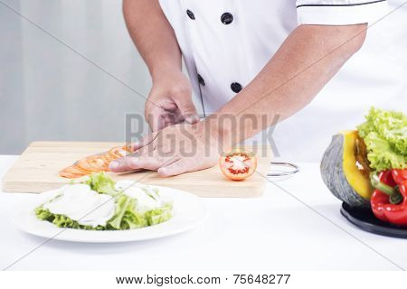 Chef's Hands Cutting Tomato