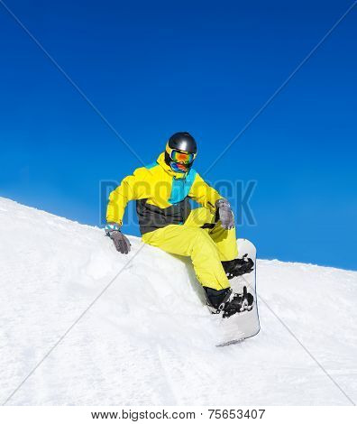 Snowboarder sitting on snow mountains