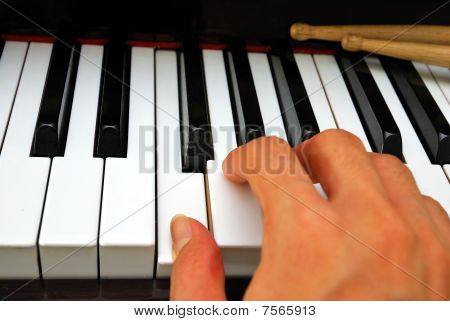 Right Hand Playing On Piano Keyboard With Drum Sticks