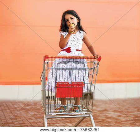 Happy Little Girl In Shopping Cart With Tasty Ice Cream In The City