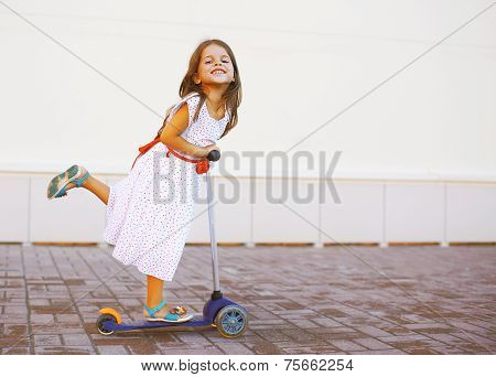 Happy Positive Child In Dress On The Scooter In The City
