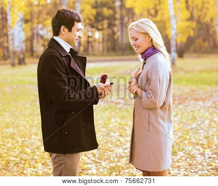 Love, Couple, Relationship And Engagement Concept - Man Proposing To A Woman In The Autumn Park Outd