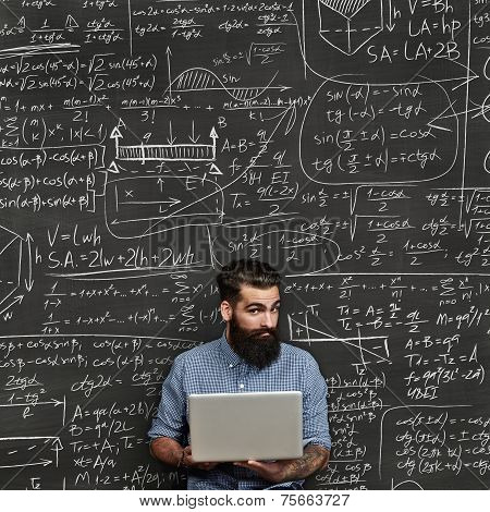 Bearded Man With Laptop. Chalkboard Background With Formulas.