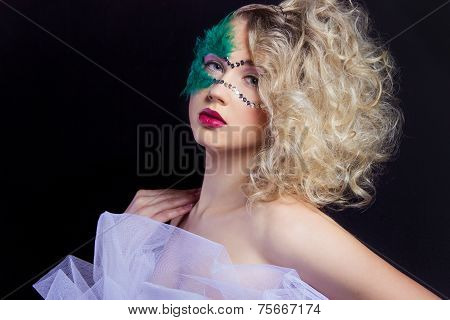 The beautiful young woman in a green mysterious venetian mask a new year carnival Christmas