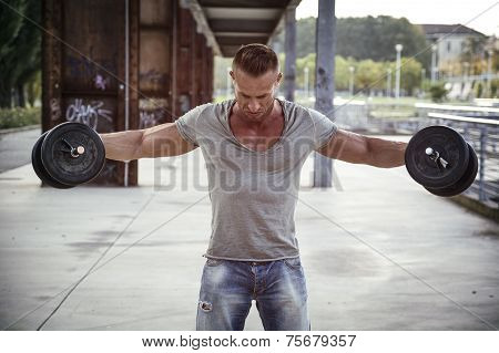 Attractive Muscular Hunk Man Lifting Weights Outdoor