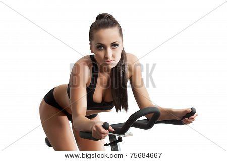 Sexy female athlete exercising on stationary bike