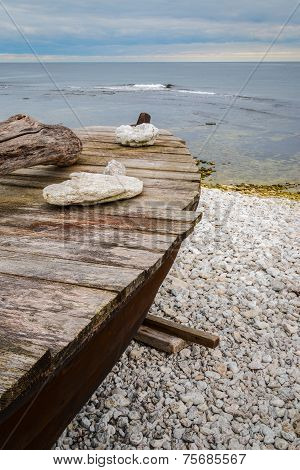 Skiff boat on stone beach by the ocean