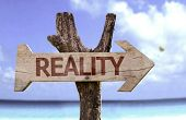 foto of realism  - Reality wooden sign with a beach on background  - JPG