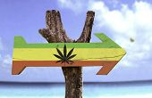 stock photo of rasta  - Rasta Flag With Marijuana Leaf sign with a beach on background  - JPG