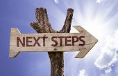 stock photo of guess  - Next Steps wooden sign on a beautiful day - JPG